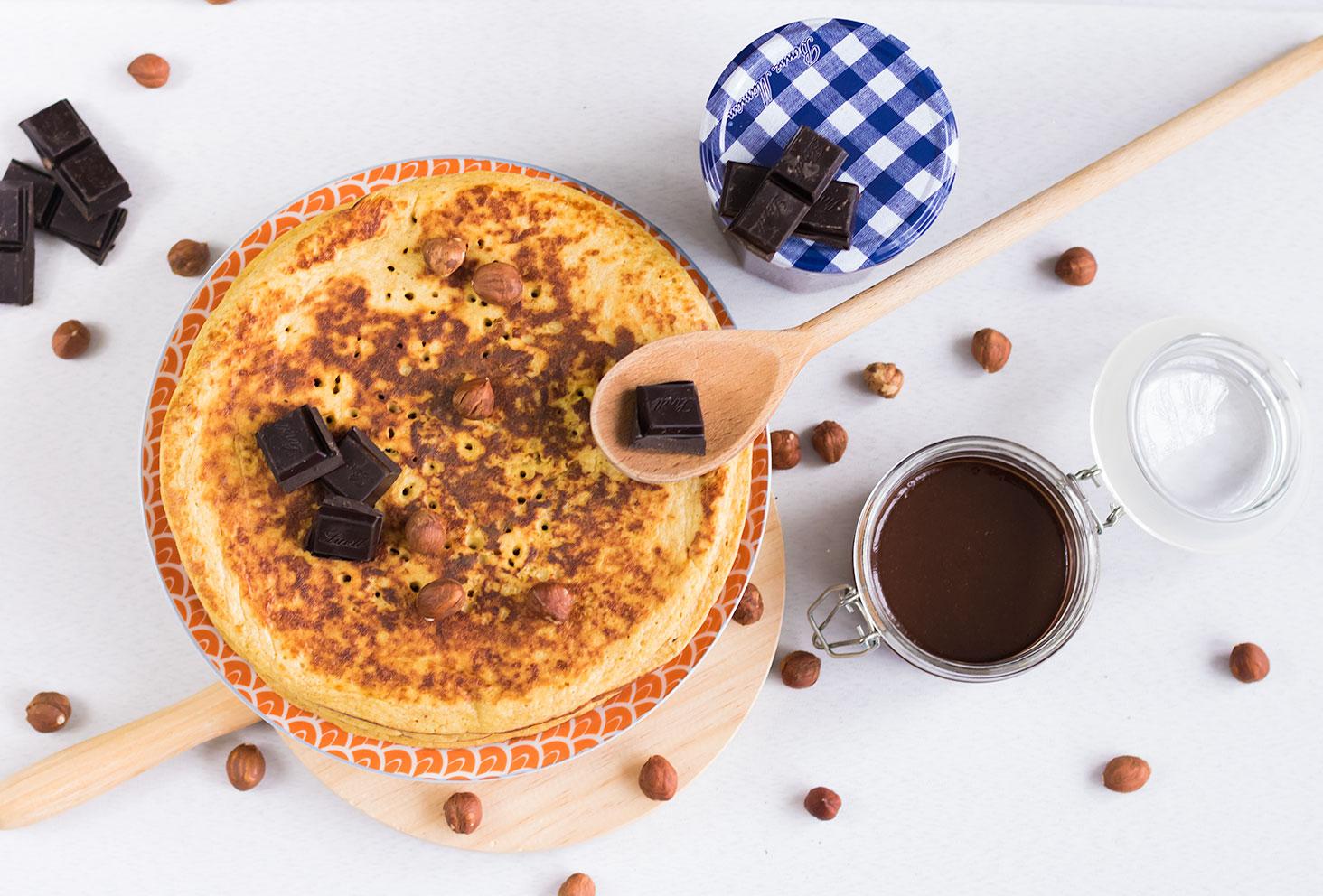 Crêpes et pâte à tartiner maison ensemble vue de haut, entourés de noisettes et de carreaux de chocolat noir