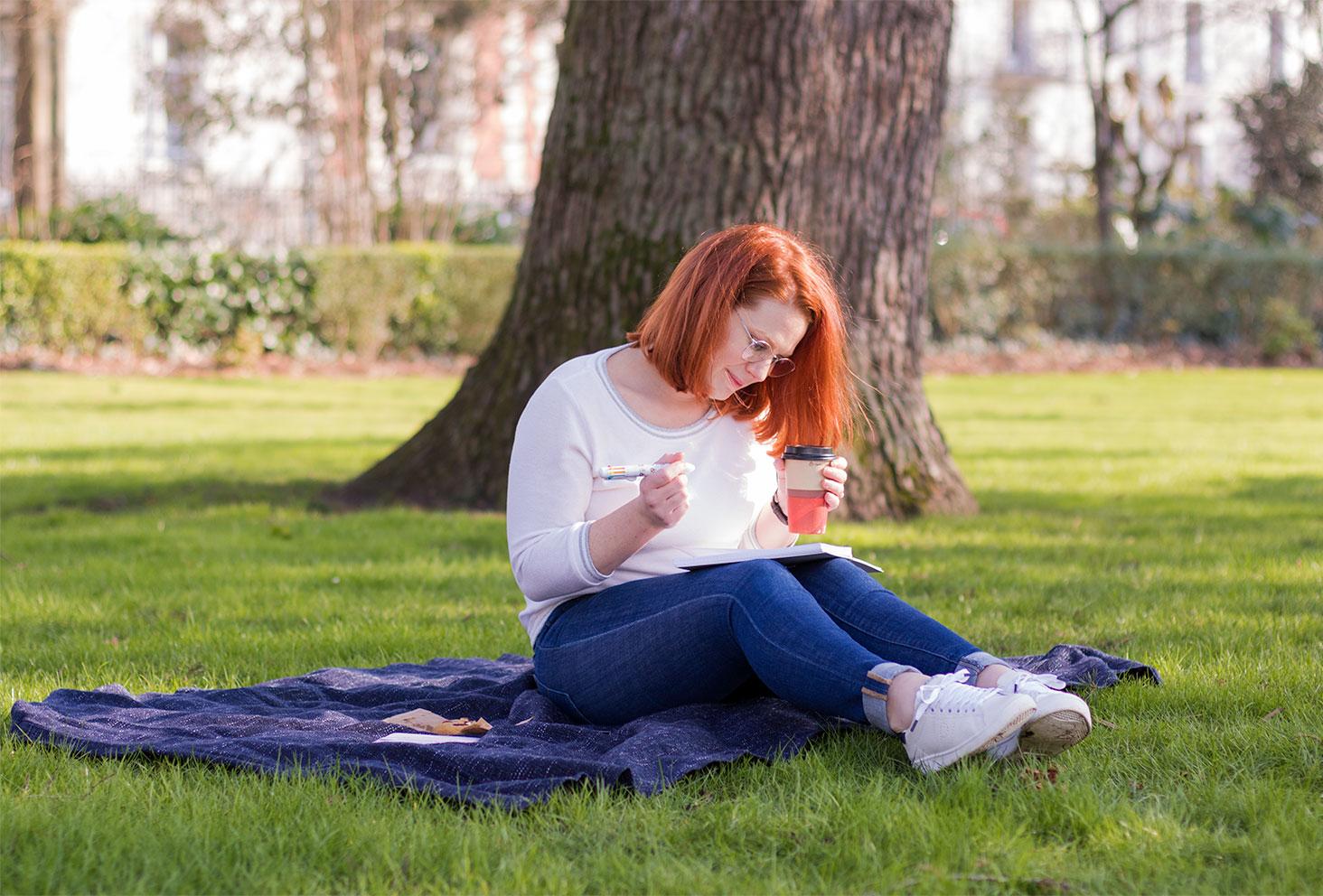 Assise au soleil sur un plaid dans l'herbe avec un café, entrain d'écrire le premier bilan de formation dans le carnet ouvert sur les genoux