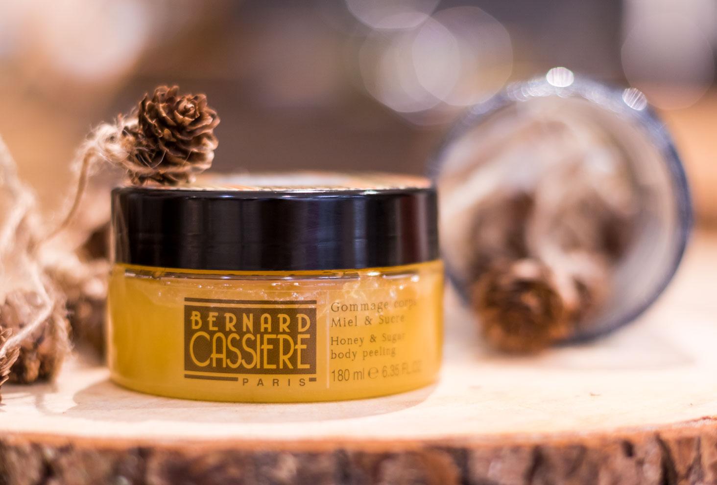 Le gommage corporel miel et sucre Frisson de Laponie de Bernard Cassière sur un décor en bois entouré de pommes de pin
