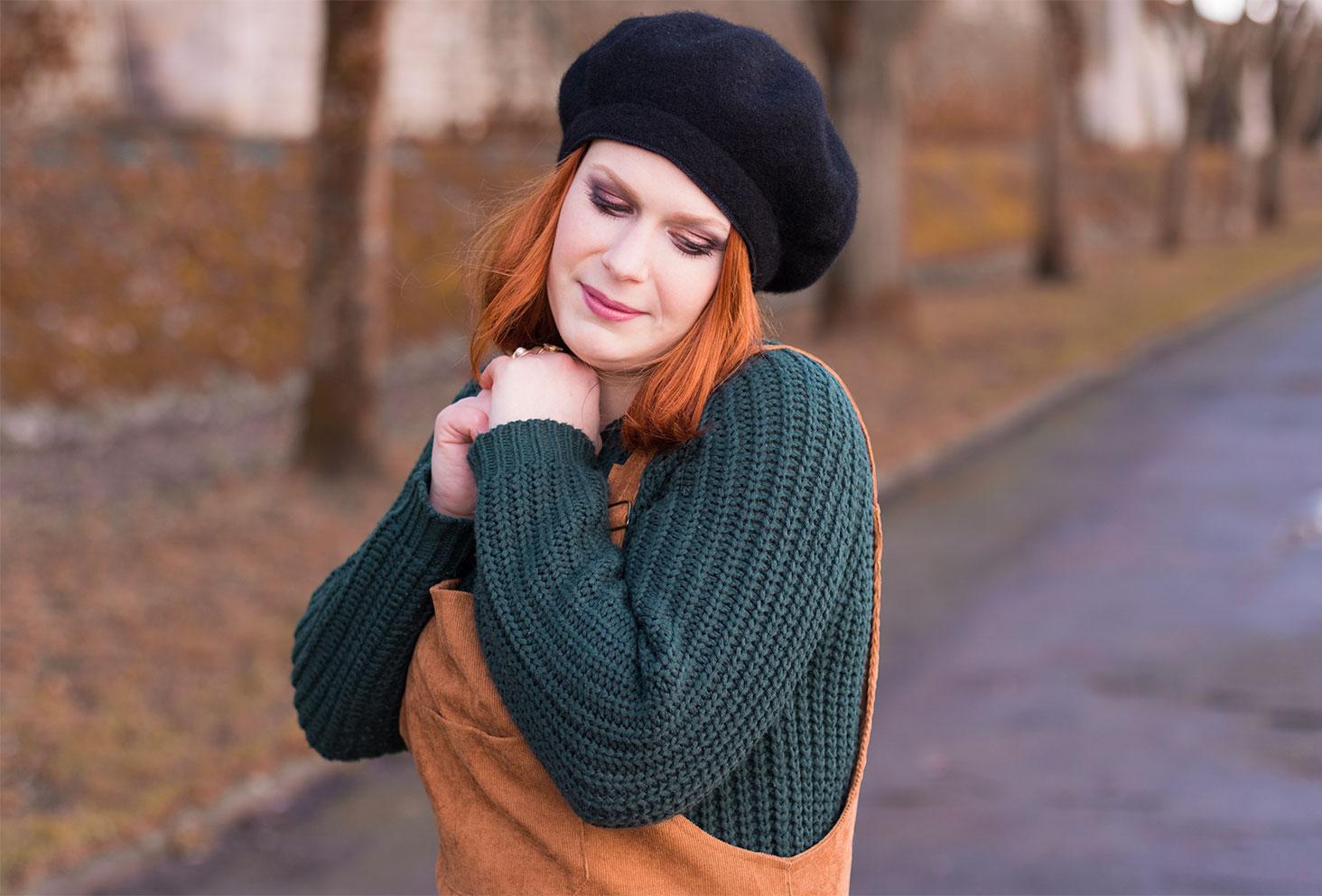 Zoom sur les grosses mailles du pull vert sapin sous la robe salopette en velours