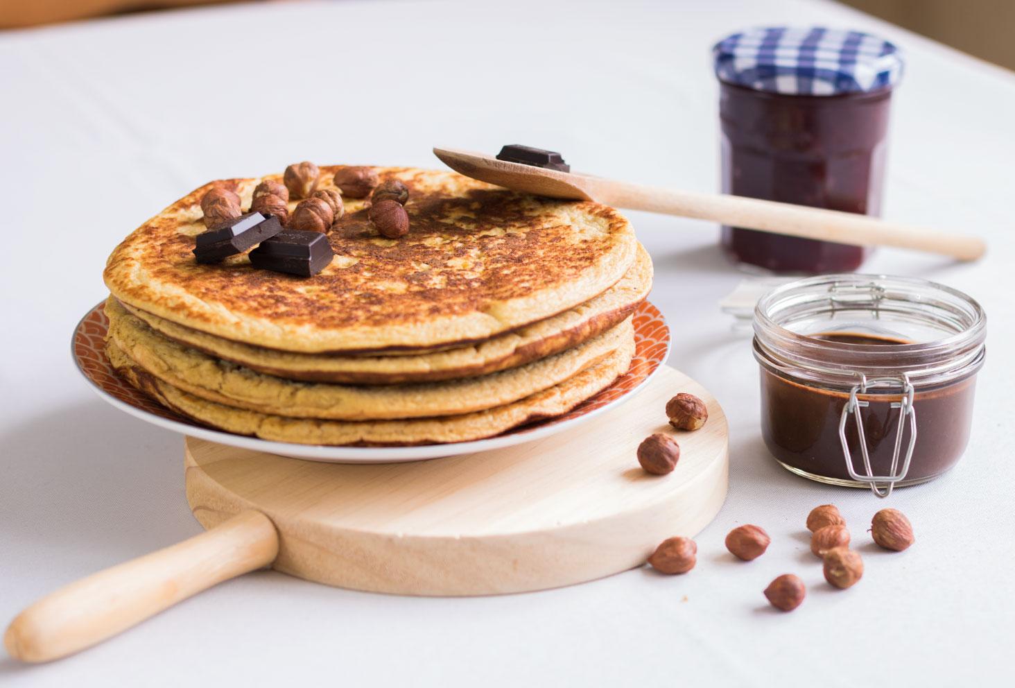 Des crêpes à la compote de pommes et de la pâte à tartiner maison chocolat et noisettes sur une table grise entouré d'instruments en bois