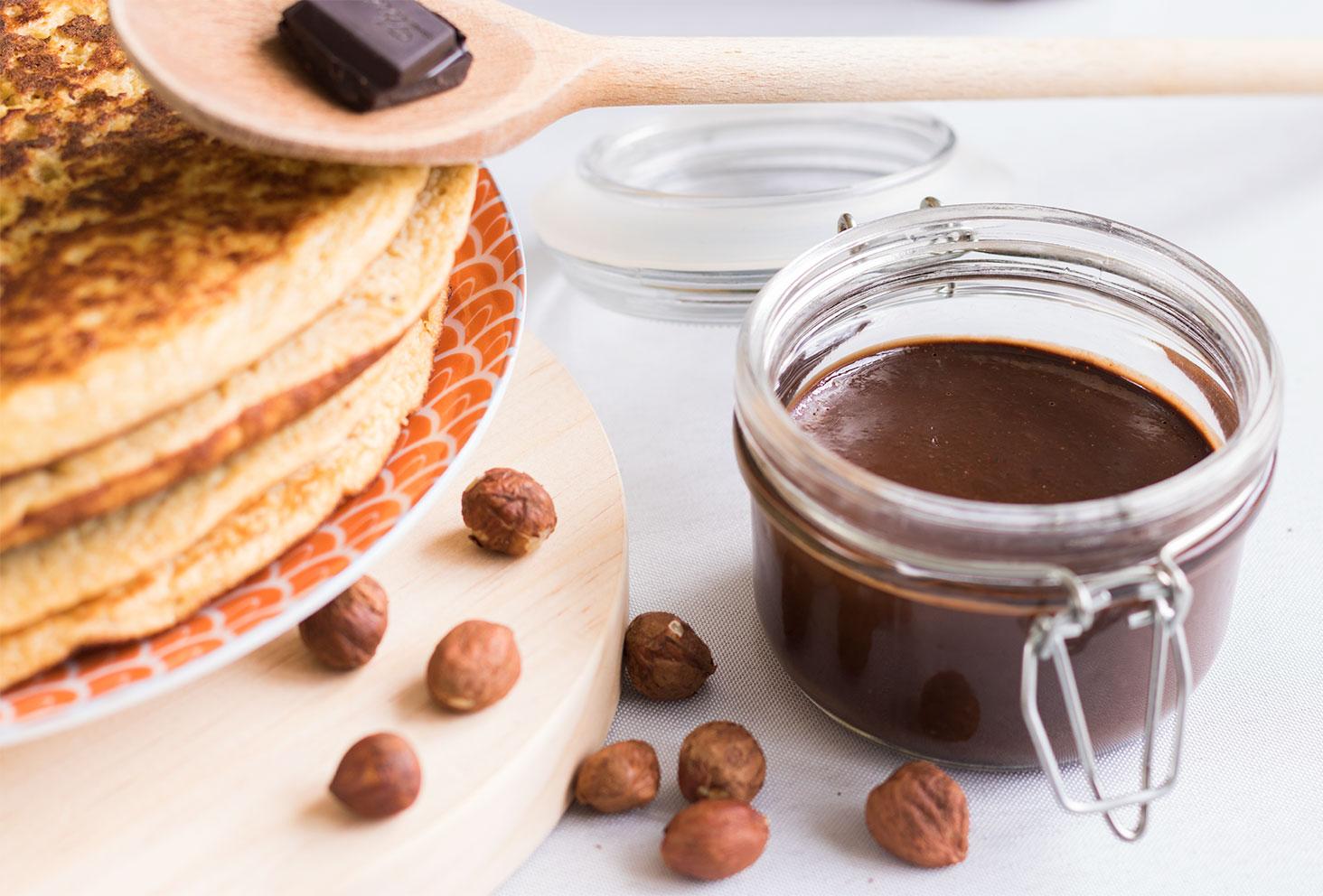 De la pâte à tartiner maison chocolat et noisettes dans un pot en verre entourée de noisettes entières et d'une cuillère en bois