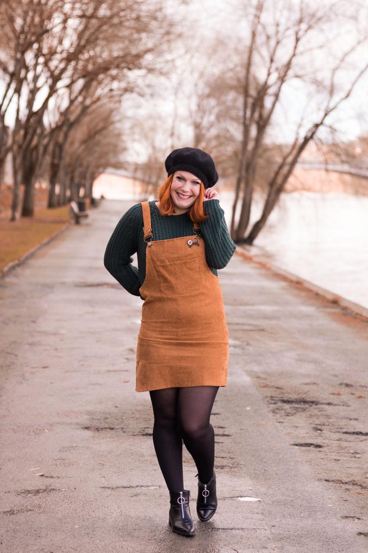 Look en robe salopette et pull cocooning, bottines noires et béret en laine noire