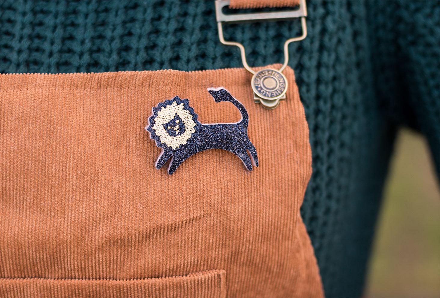 Zoom sur la broche lion pailletée noire et dorée sur la robe salopette camel en velours
