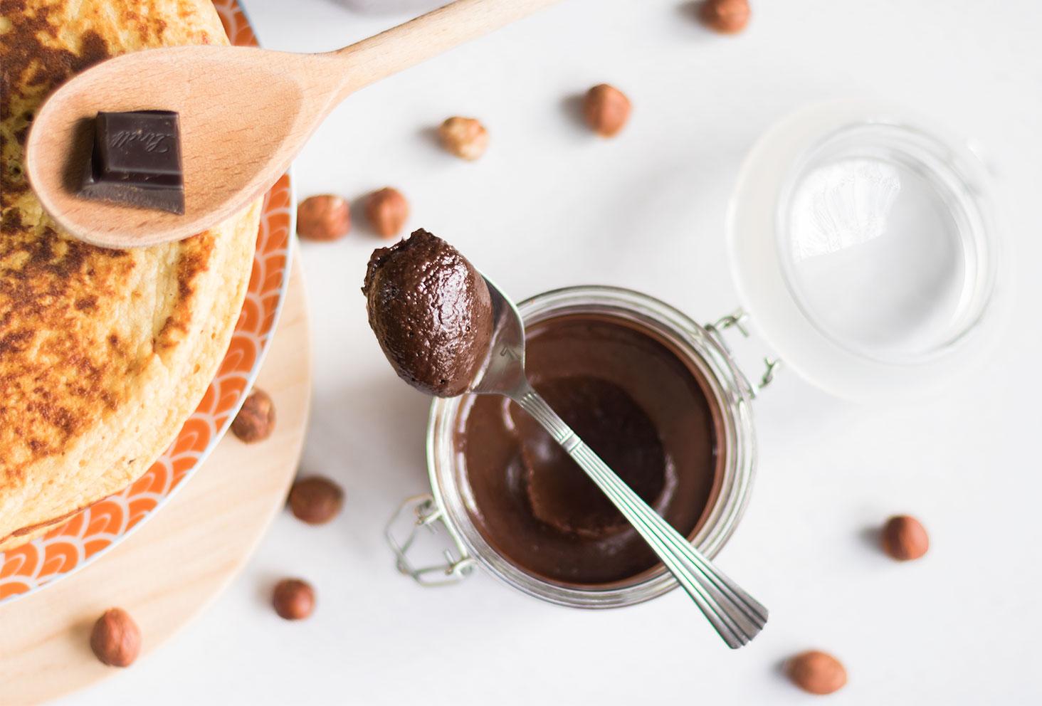 Pâte à tartiner au chocolat et à la noisettes, fondantes dans une cuillère en argent déposée sur le pot en verre