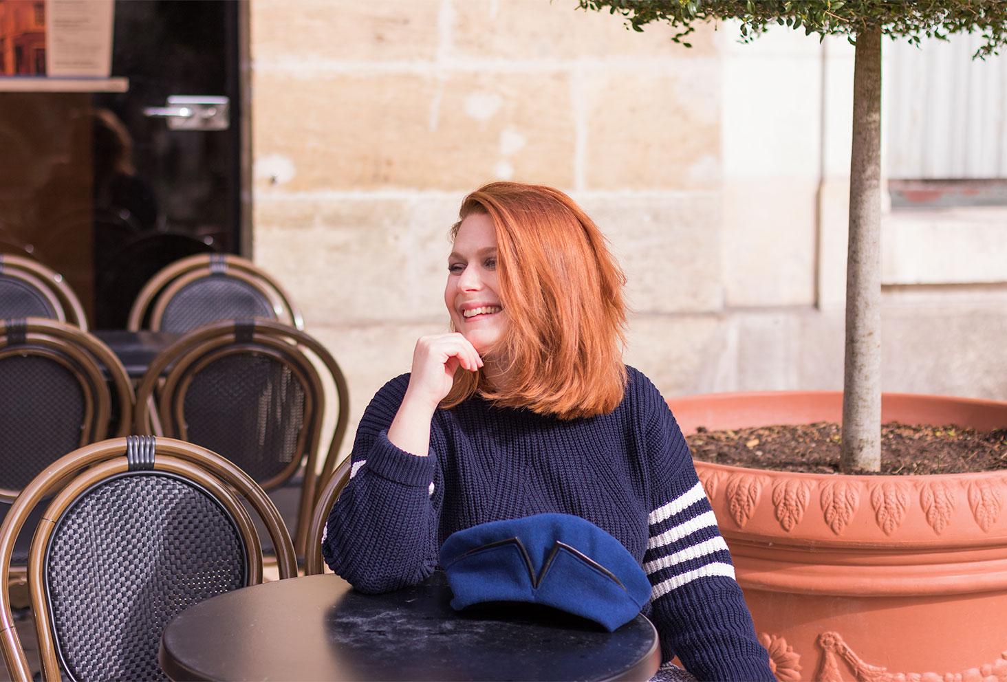 Assise à la terrasse d'un café avec le sourire et le béret bleu Falbalas posé sur la table