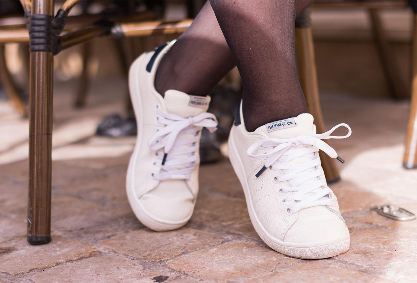 Zoom sur les baskets blanche Pepe Jean sur les pavé assise à la terrasse d'un café