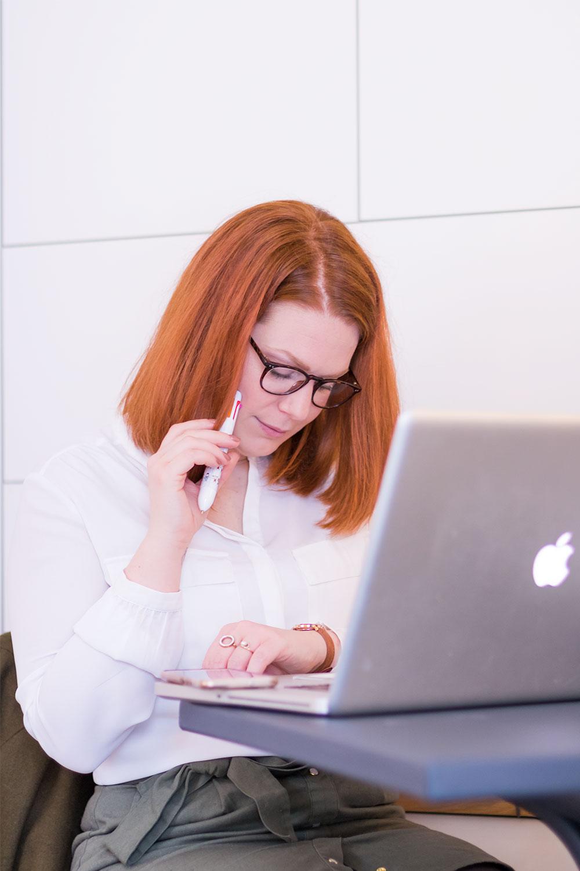 Chemisier blanc, lunettes et stylo en main, en pleine réflexion du second bilan de formation