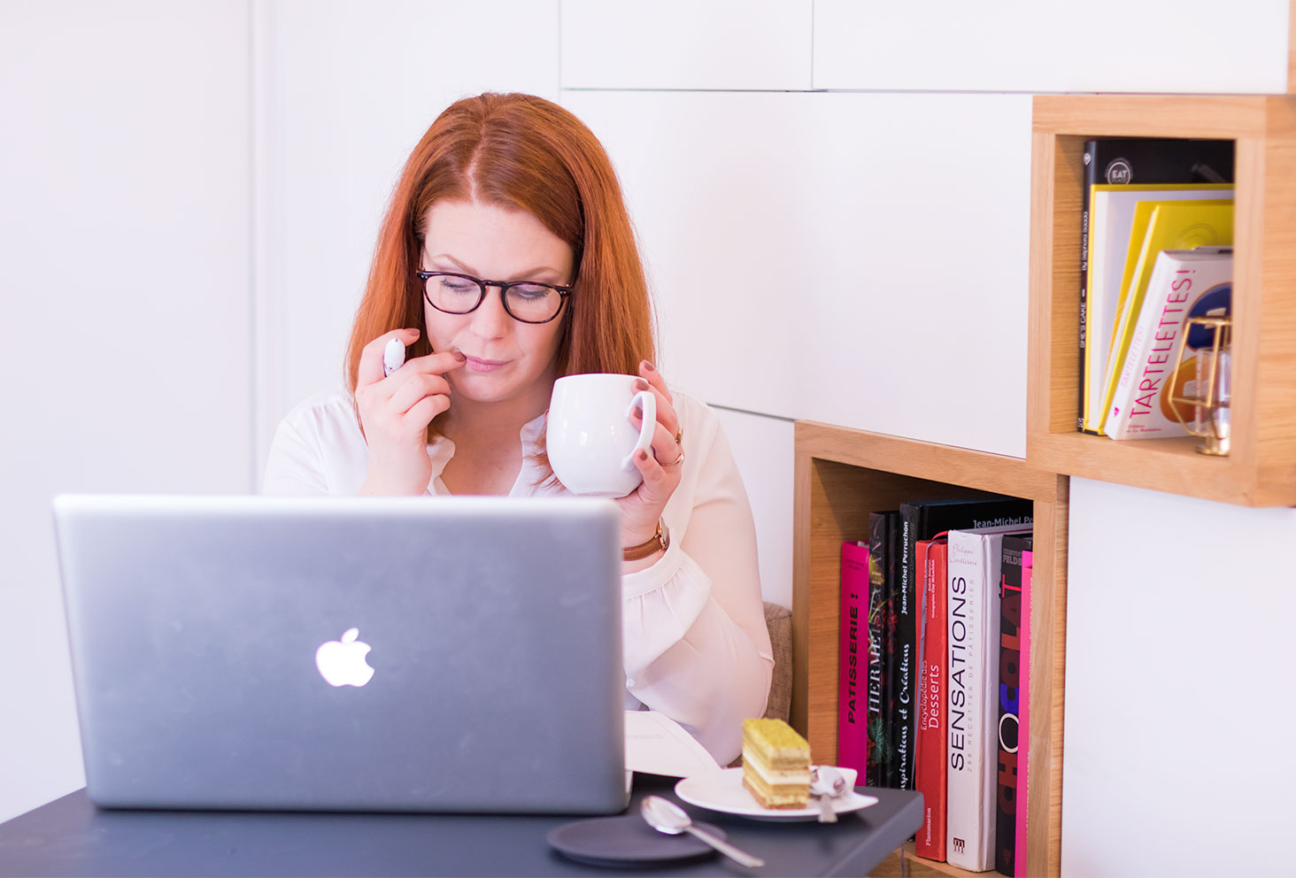 En plein réflexion devant l'ordinateur avec un thé dans la main pour le second bilan de formation