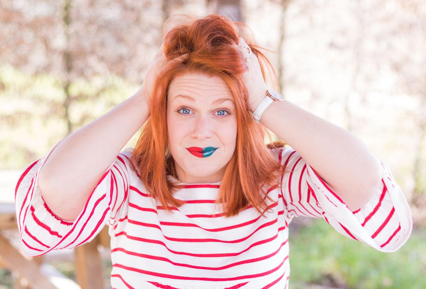 Mains sur la tête en pleine réflexion, avec un rouge à lèvres bicolore en marinière rouge, pour le défaut 2