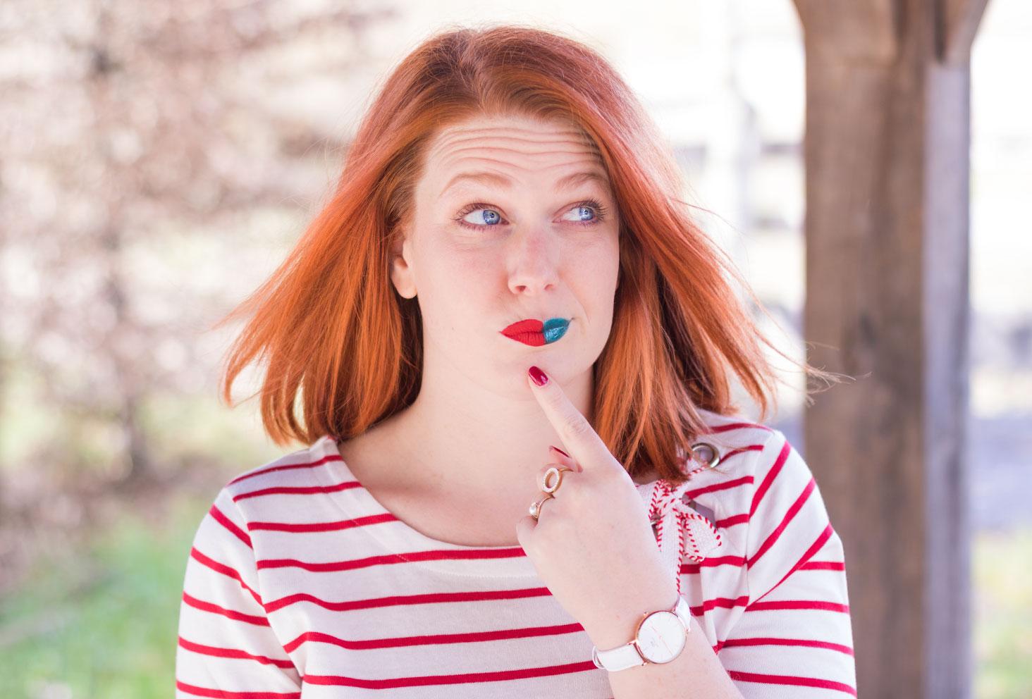 En pleine réflexion le doigt sur le menton dans une marinière rouge et un rouge à lèvres bicolore rouge et bleu, pour le nouveau problème : l'indécision