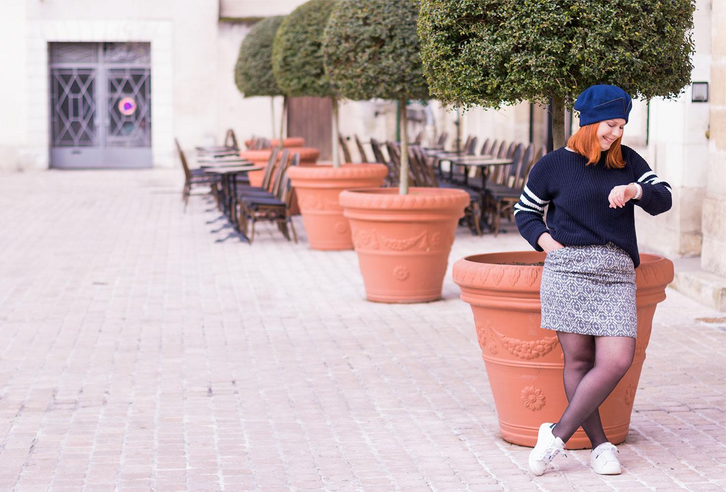 Appuyé contre un pot de fleurs géant devant la terrasse d'un café vide regardant l'heure