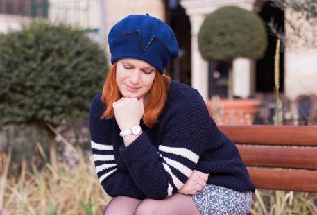 Assise sur un banc accoudée sur les genoux dans un look en camaïeu de bleu