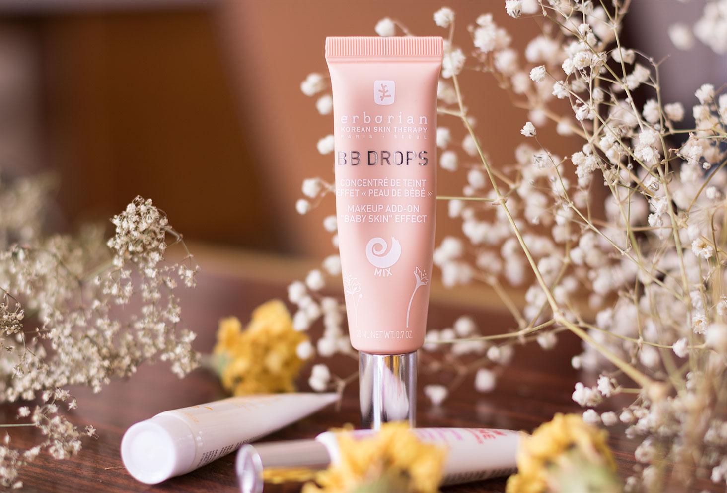 La BB Drops par Erborian dans son packaging rose poudré posée sur une table en bois et entourée de fleurs séchées