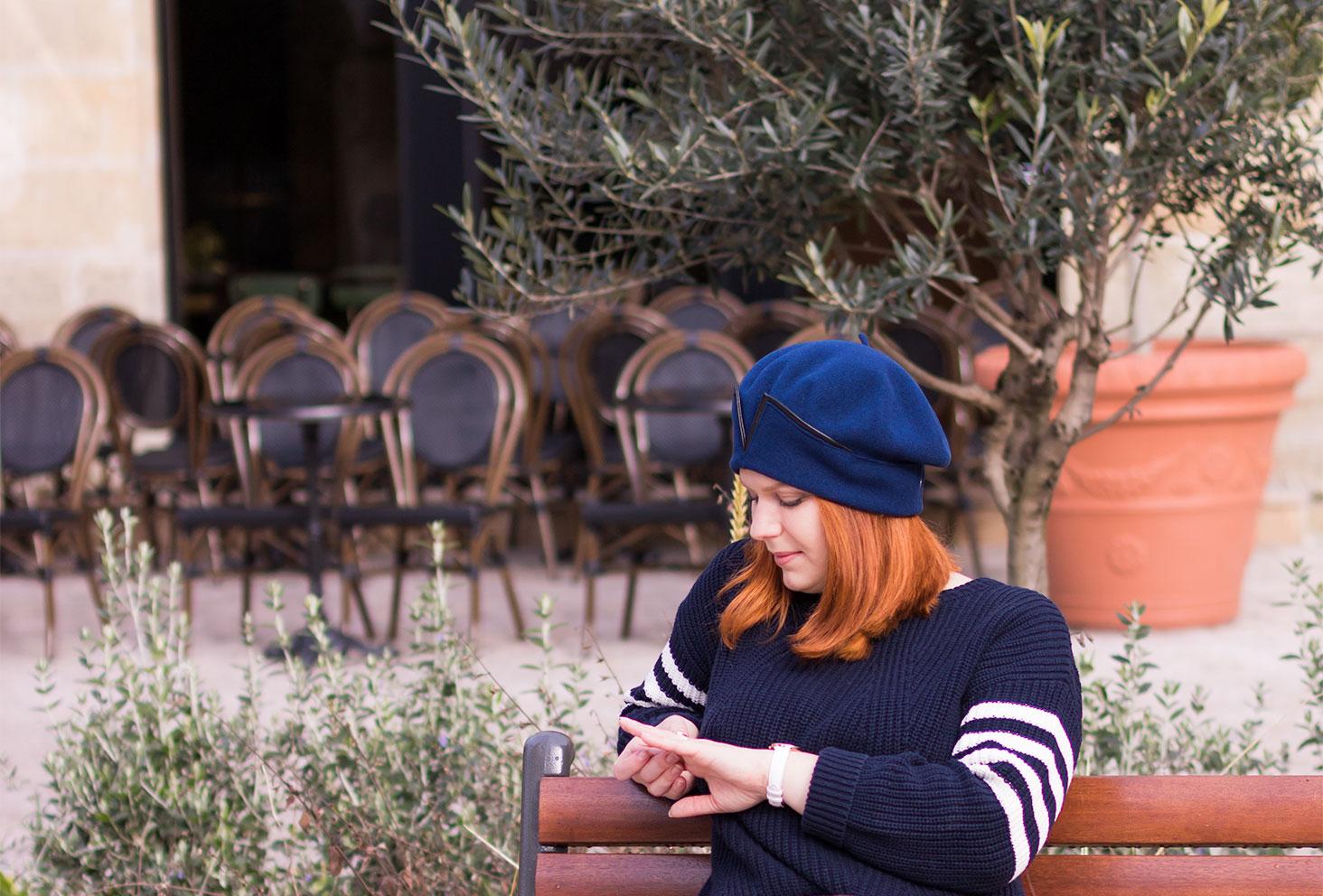 Assise sur un banc à l'avant d'une terrasse de café portant un béret bleu Falbalas