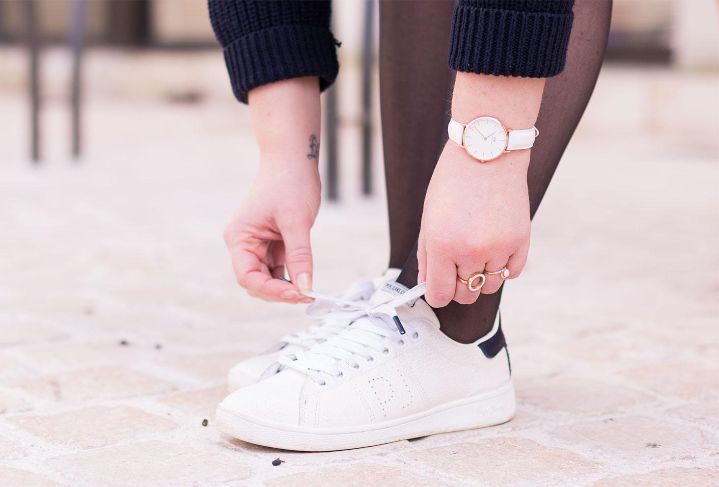 Zoom sur la montre Daniel Wellington et les chaussure Pepe Jean entrain d'attacher les lacets