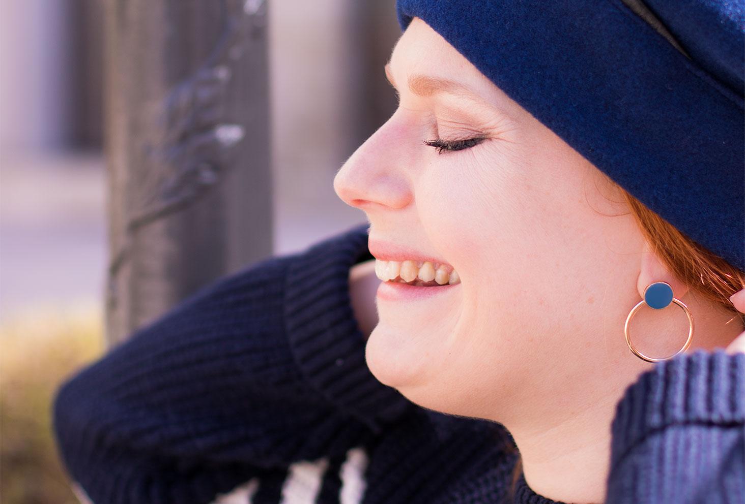 Zoom sur les boucles d'oreilles MOA bleu avec le sourire de profil