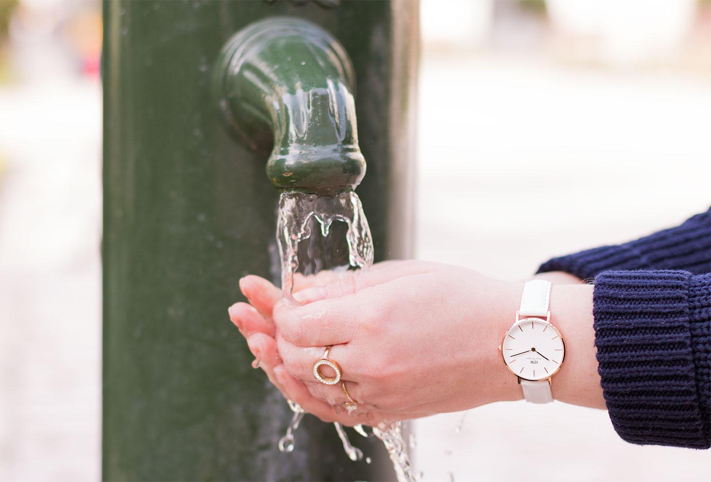 Zoom sur la montre blanche Daniel Wellington les mains sous l'eau d'une fontaine extérieure