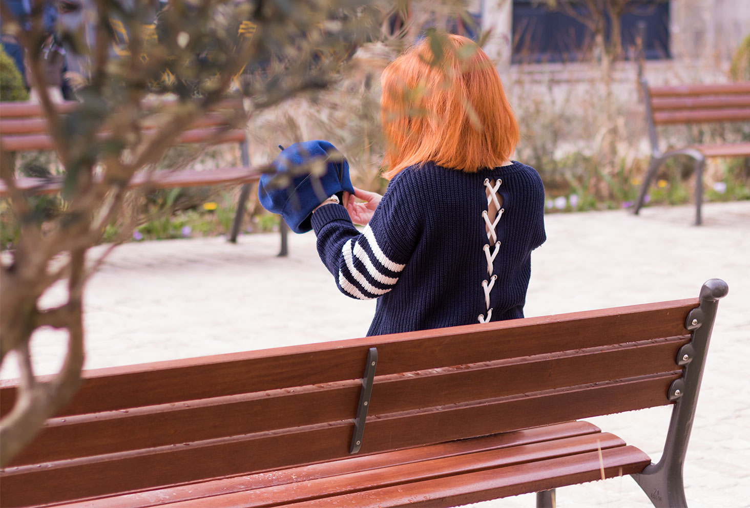 Le dos ouvert du pull bleu Etam assise sur un banc avec un béret dans les mains