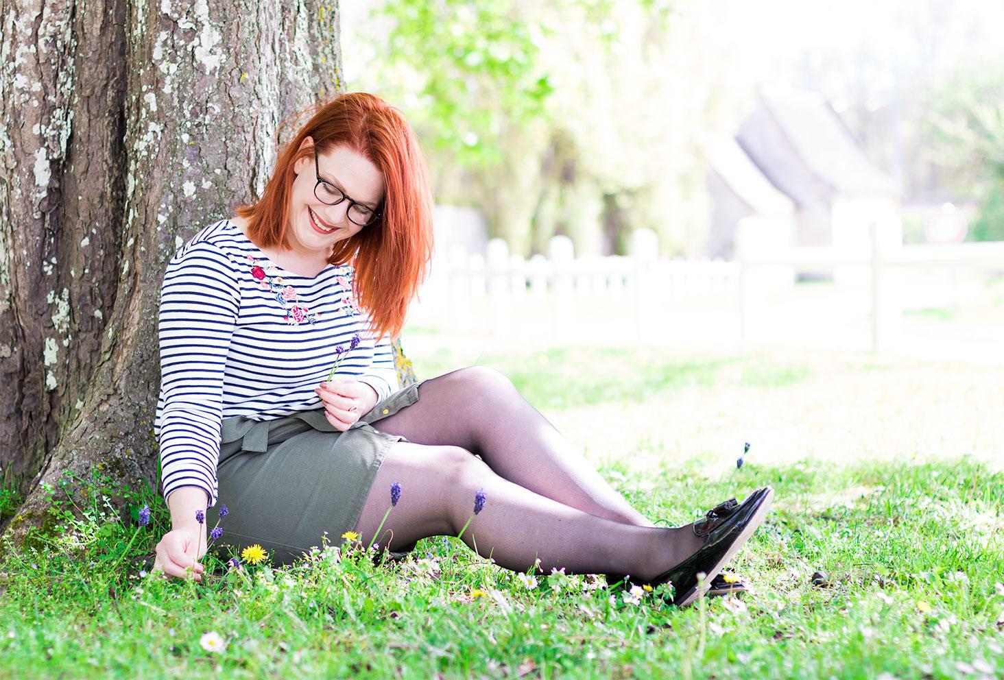 Assise dans l'herbe contre un arbre en marinière et jupe kaki pour le look de la FAQ