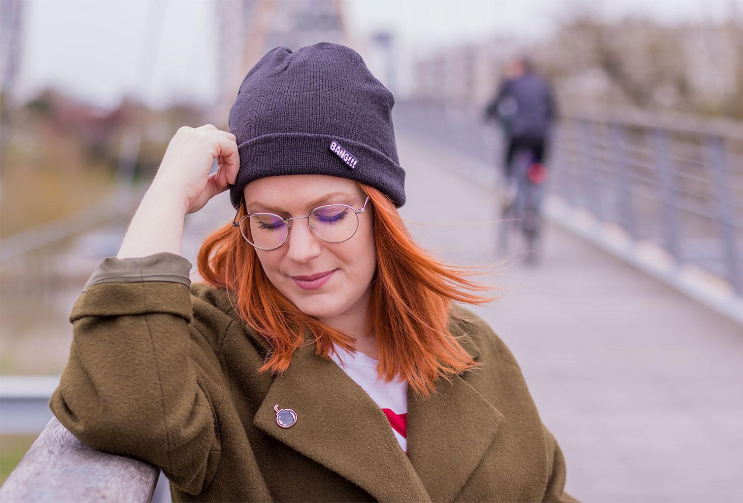 Bonnet noir et pin's BANG, lunettes vintage et manteau kaki pin's bombe pour un look street