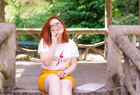 Assise sur les marches du jardin des Prébendes au téléphone pour le dernier bilan de formation