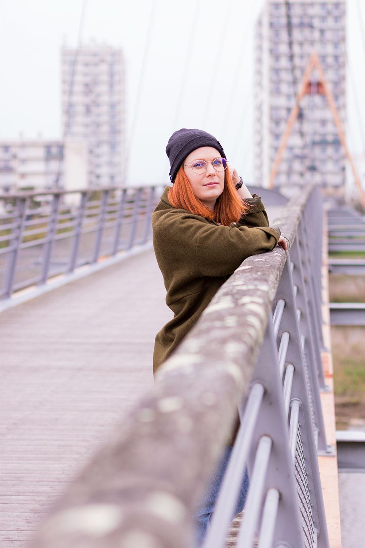 Street style accoudée à la rembarde d'un pont suspendu