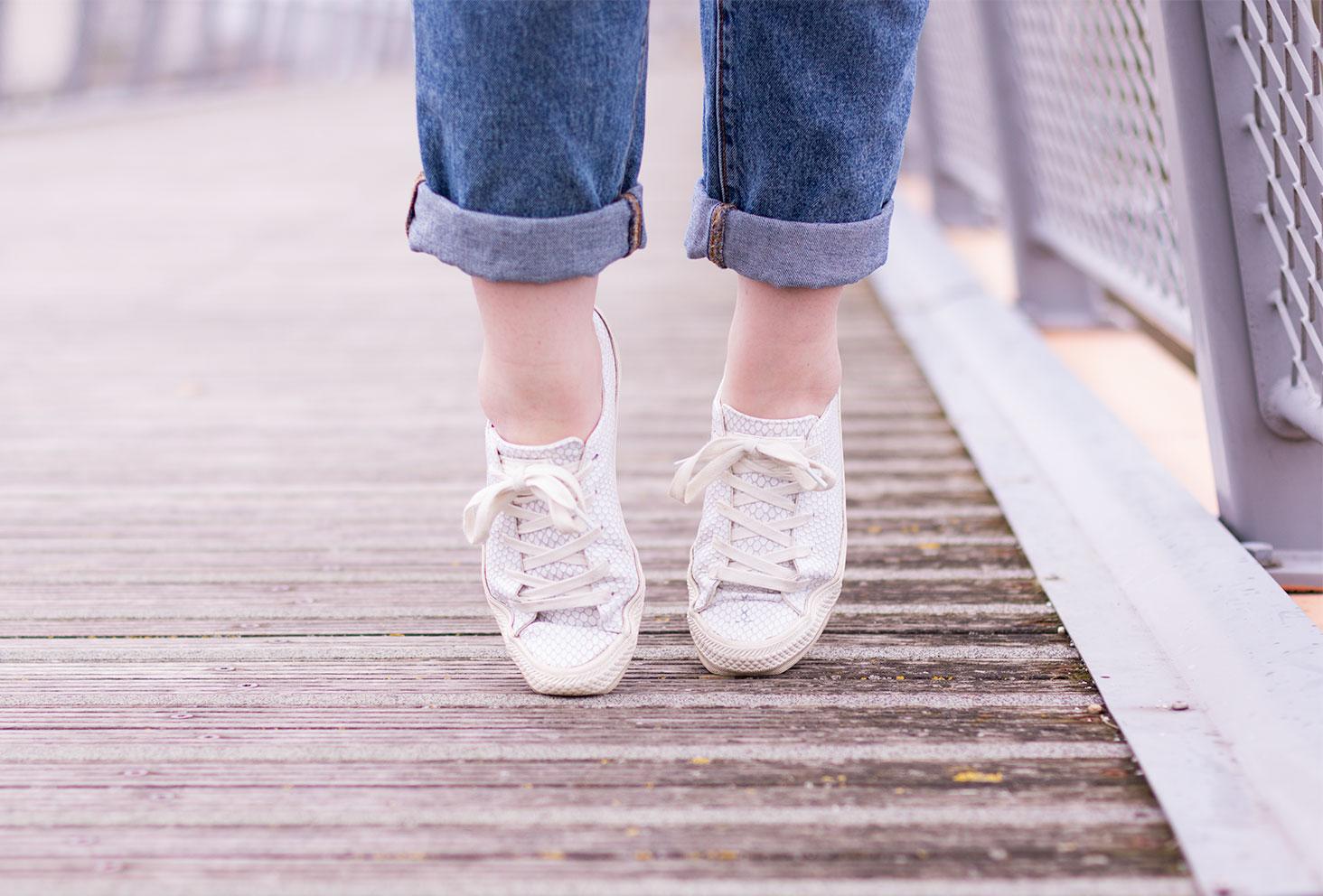 Converse en cuir grises sur la pointe des pieds sur un pont en bois et en métal