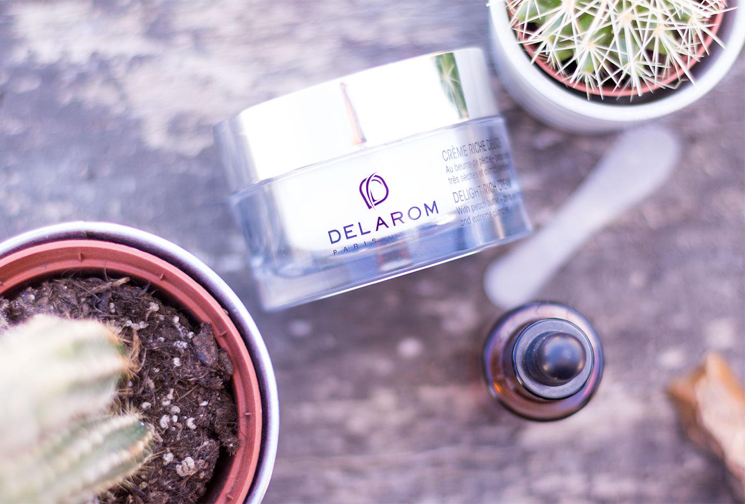 Zoom sur le packaging de la crème Riche Délice DELAROM Paris sur une planche en bois au milieu des cactus