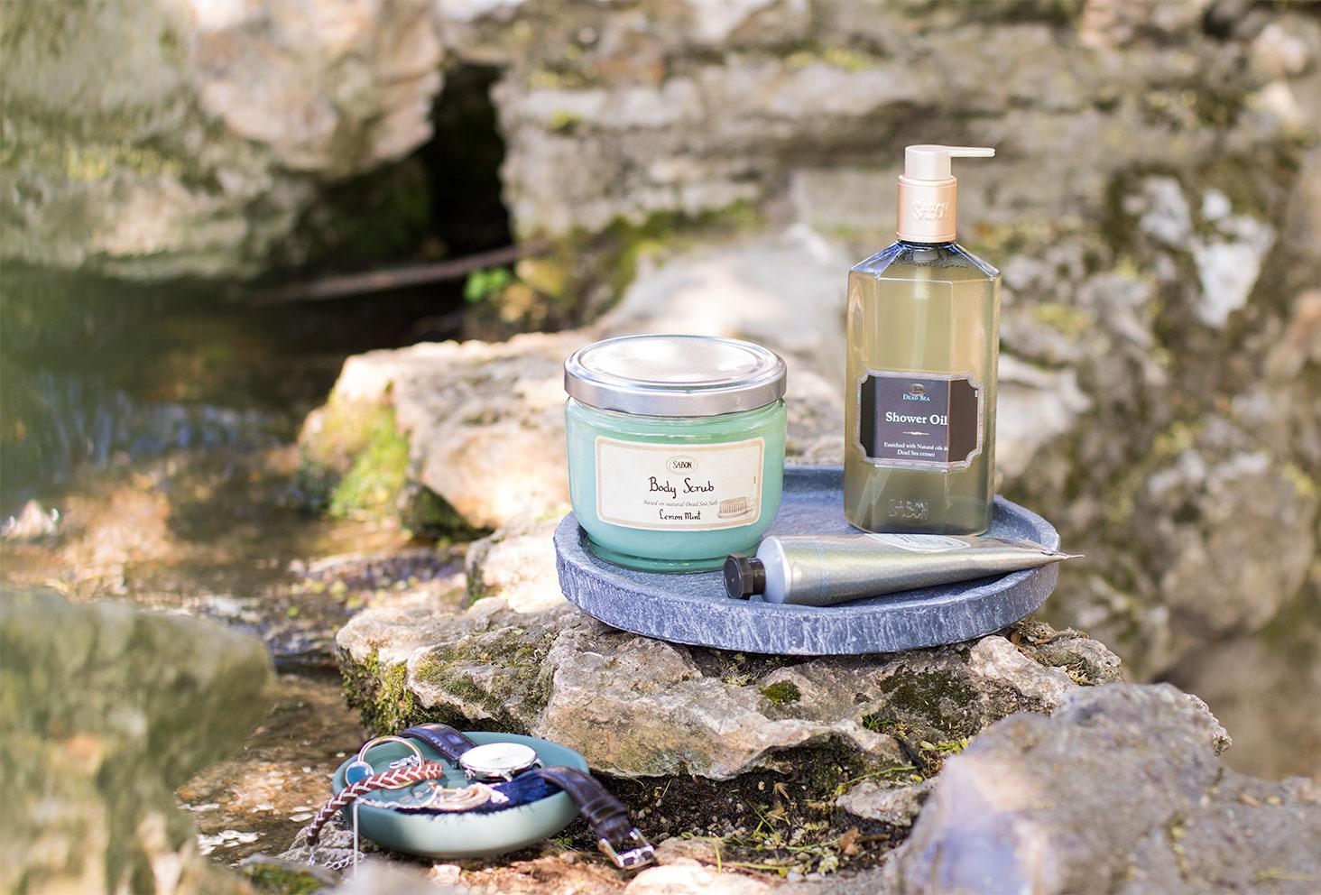Le gommage, l'huile de douche et la crème pour les mains de Sabon dans un plat en ardoise sur les rochers au bord de l'eau
