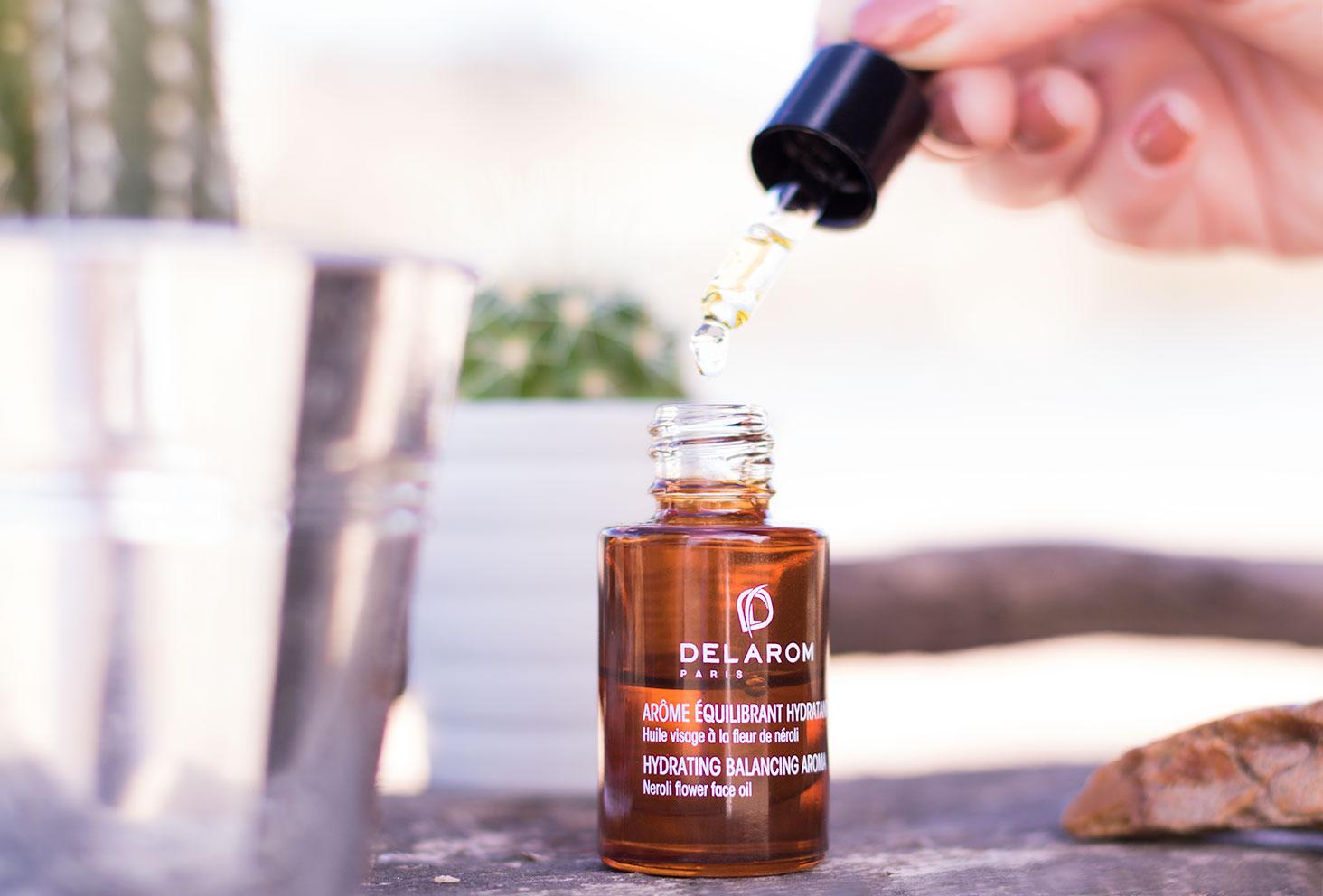 L'huile à la fleur de néroli DELAROM Paris ouvert sur une planche en bois