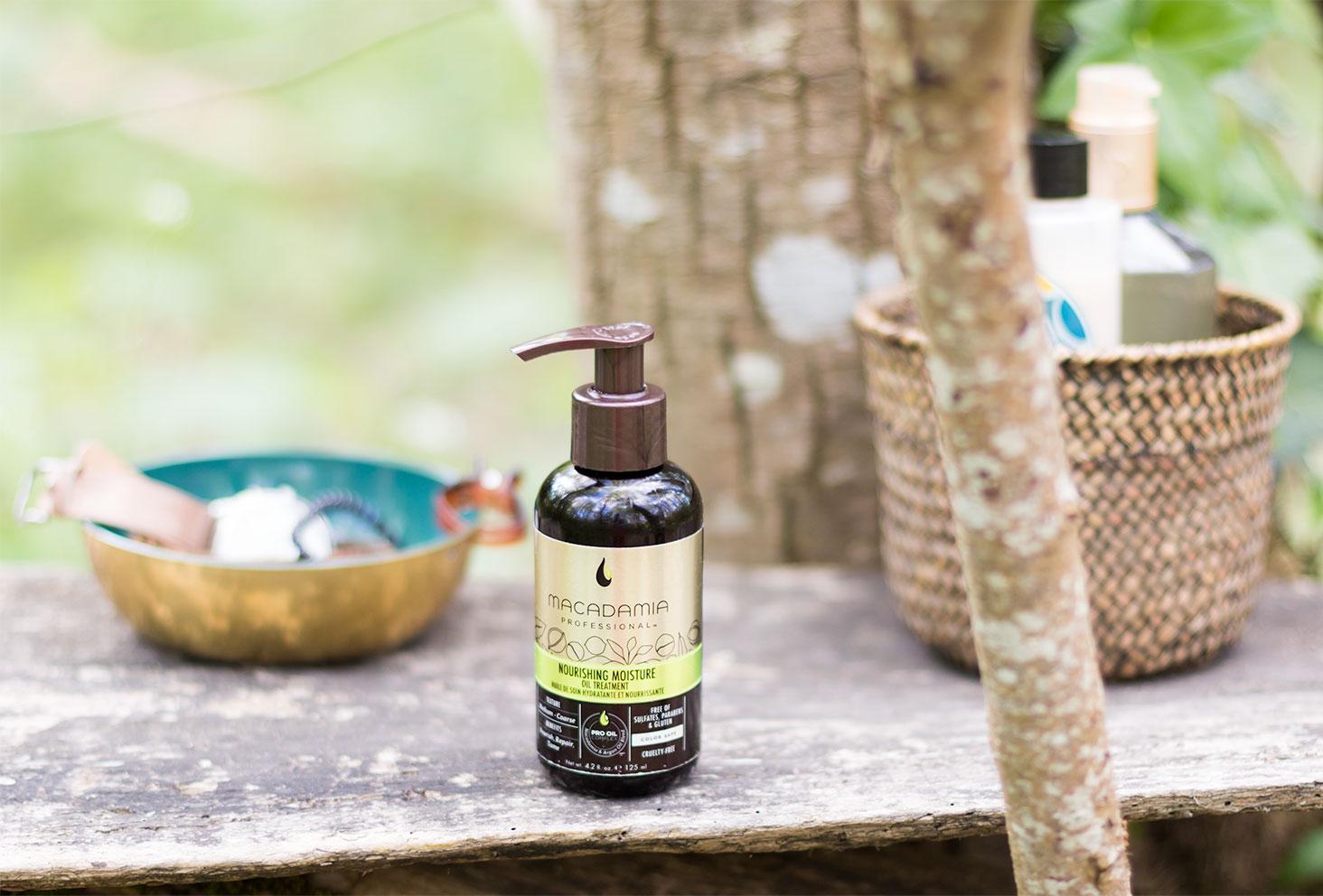 L'huile pour cheveux Macadamia Professional posé sur une planche en bois avec des produits de salle de bain