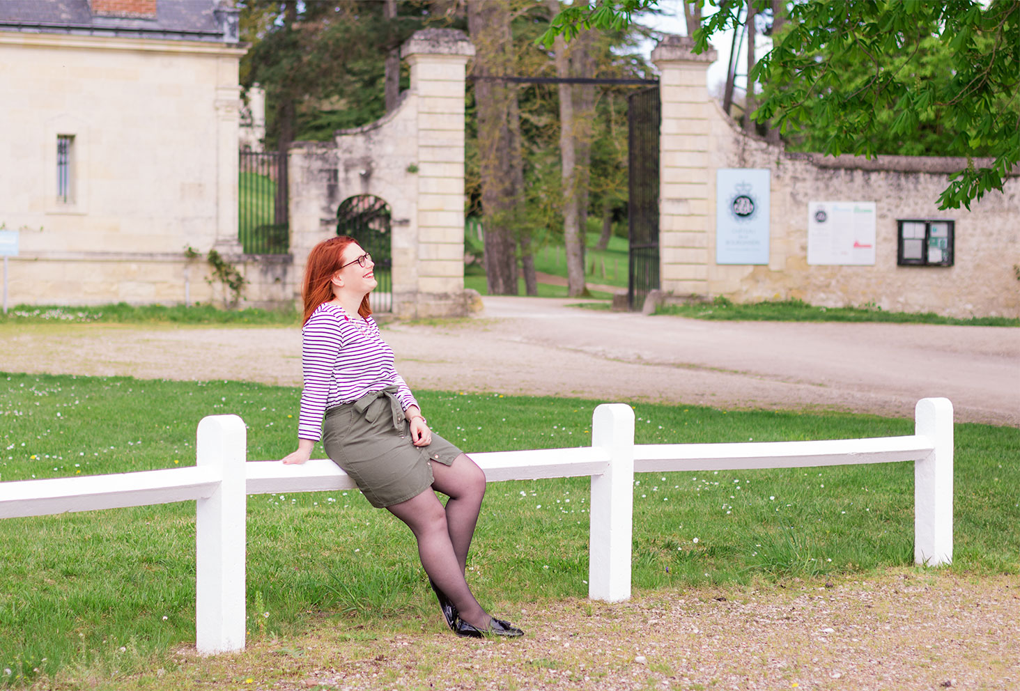 Assise sur les barrières blanches devant le château de la Bourdaisière en marinière, jupe kaki et mocassins vernis
