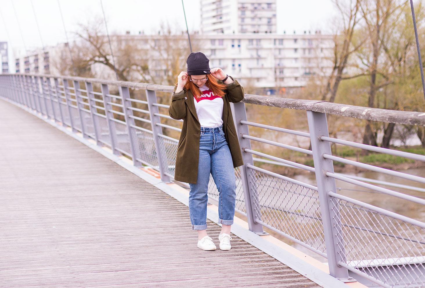 Jeans boyfriend, t-shirt Levis, baskets et bonnet sur un pont suspendu en street style