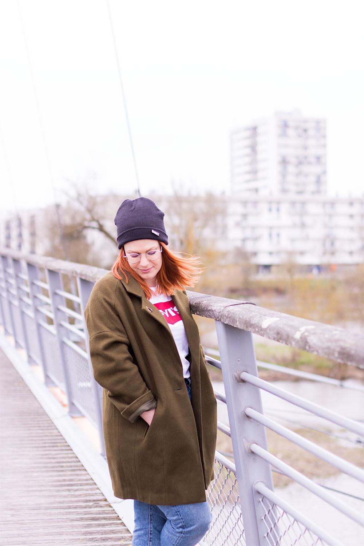 Manteau kaki porté en street style sur un pont suspendu avec les immeubles en fond