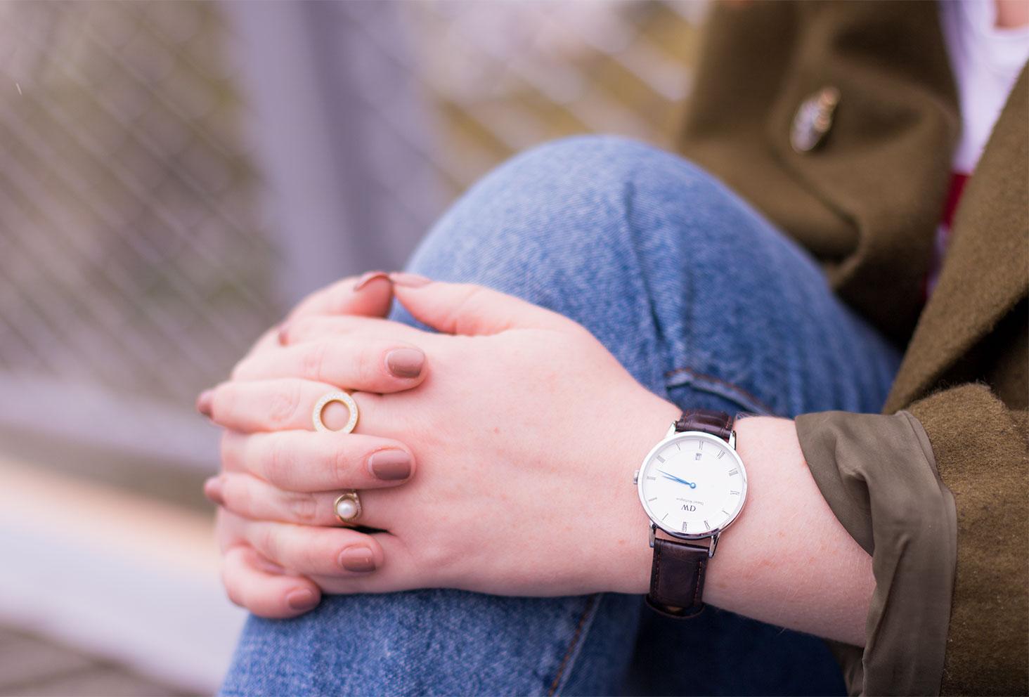 Zoom sur la montre marron avec ses aiguilles bleues de Daniel Wellington