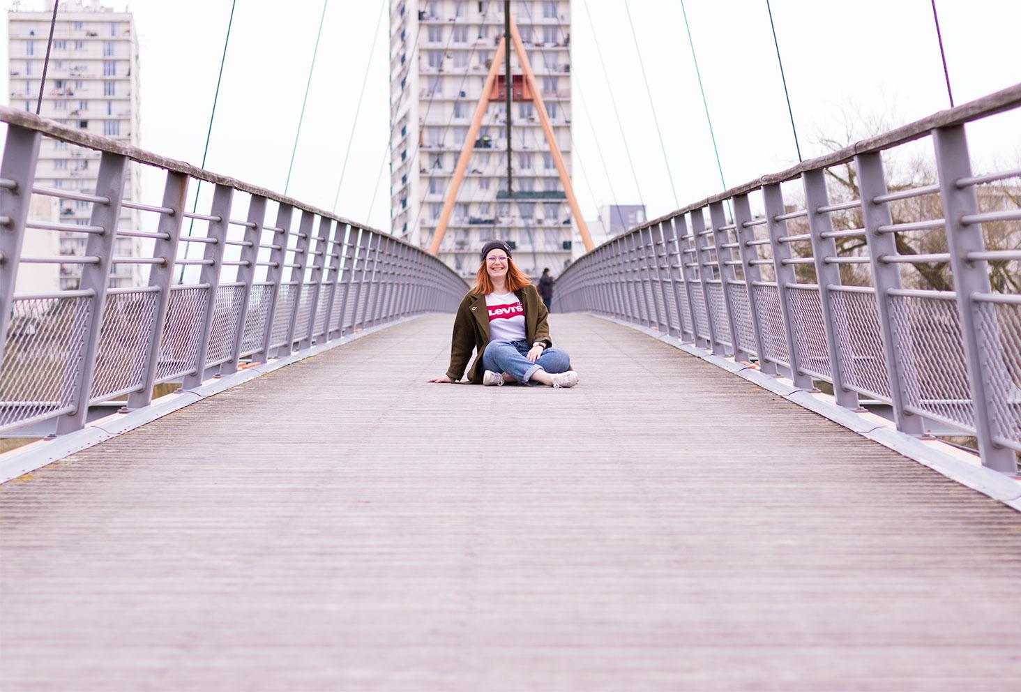 Assise sur un pont suspendu en bois et en métal en street style