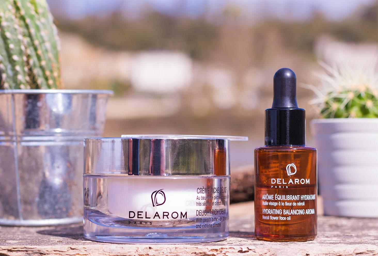 Zoom sur la crème Riche Délice et de l'arôme équilbrant hydratant de la marque DELAROM Paris sur une planche de bois au milieu des cactus