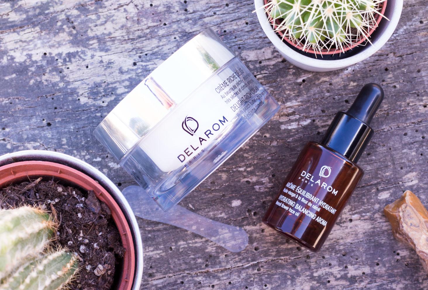 Zoom sur le packaging de la crème Riche Délice et de l'arôme équilbrant hydratant de la marque DELAROM Paris sur une planche de bois au milieu des cactus