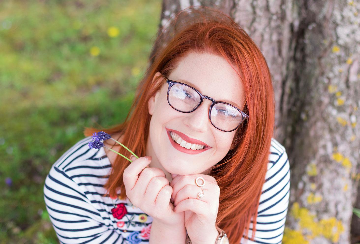 Zoom sourire et cheveux roux assise contre un arbre