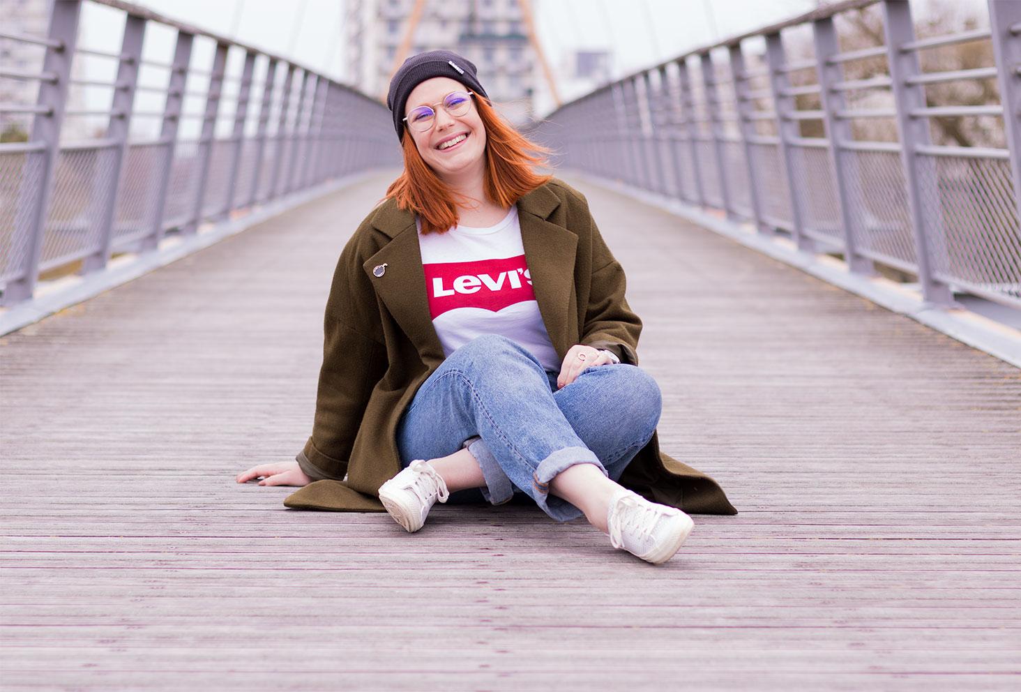 Assise sur un pont suspendu en street style