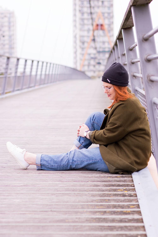 Assise sur le pont suspendu en street style de profil avec un genoux levé avec les mains