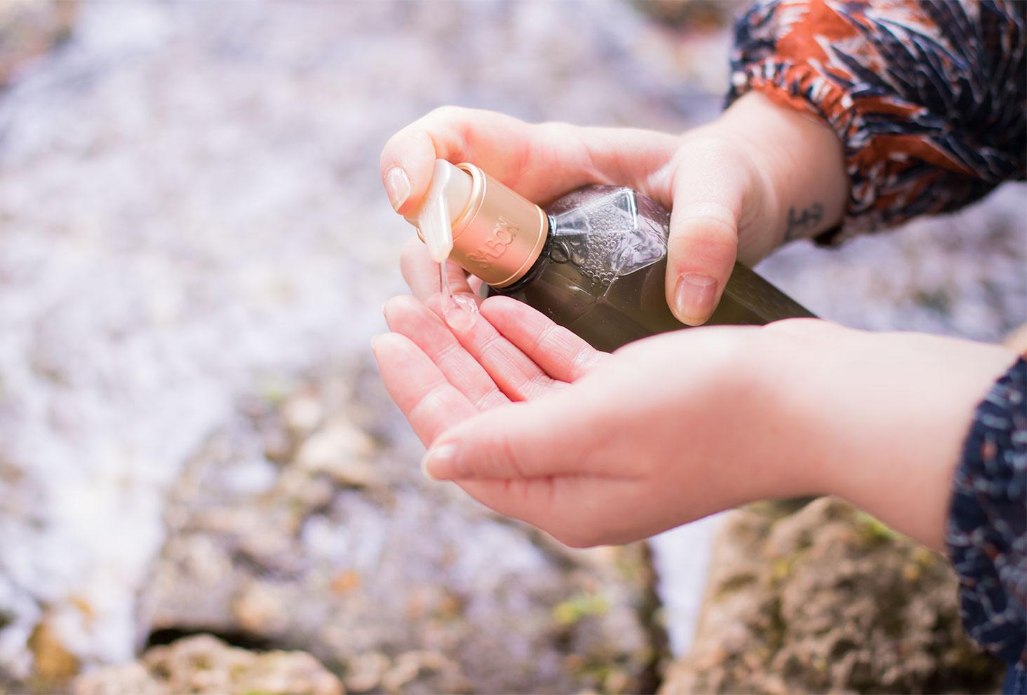 Une pompe de produit dans les mains au bord de l'eau pour le top 3 des gels douche