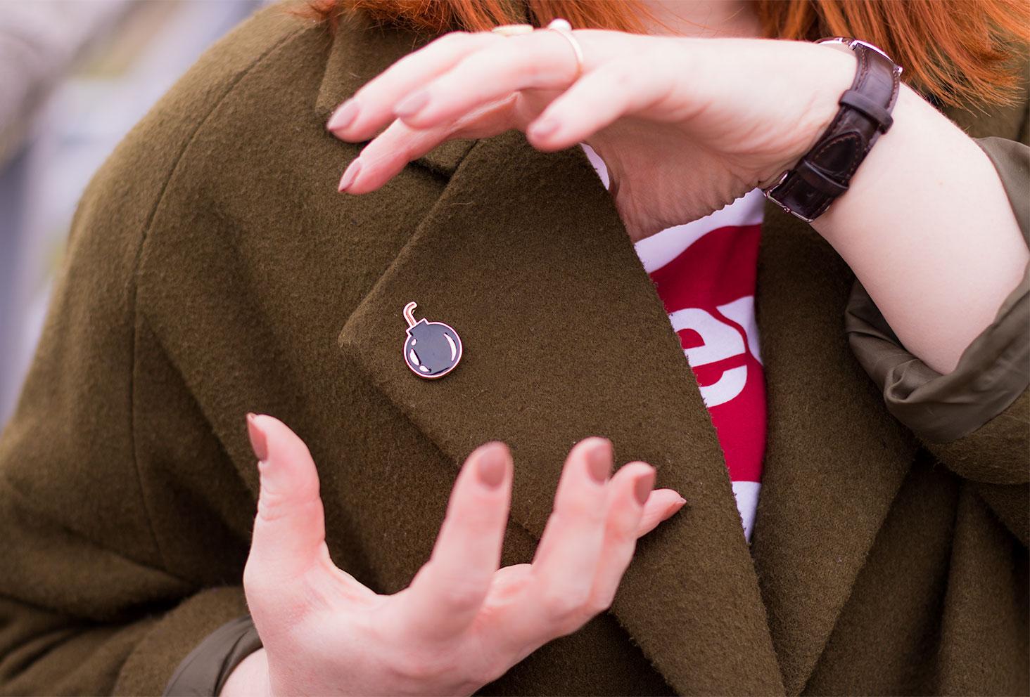 Zoom sur un pin's en forme de bombe accroché au manteau kaki du look street
