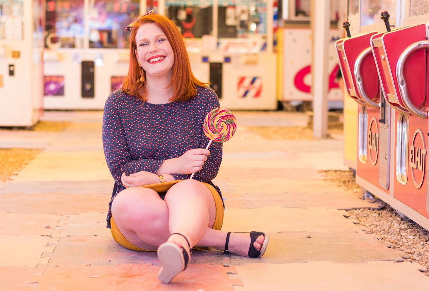 Assise sur le sol jaune et rouge, en blouse La Morue à la fête foraine
