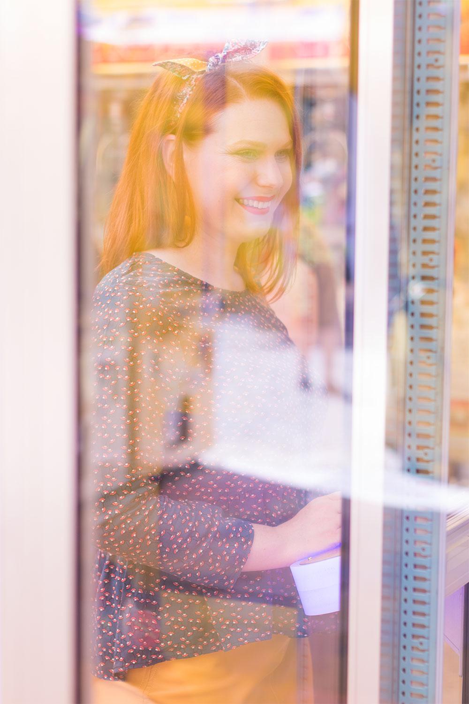 Sourire et look blouse et jupe derrière la vitre d'une machine à grappins de la fête foraine