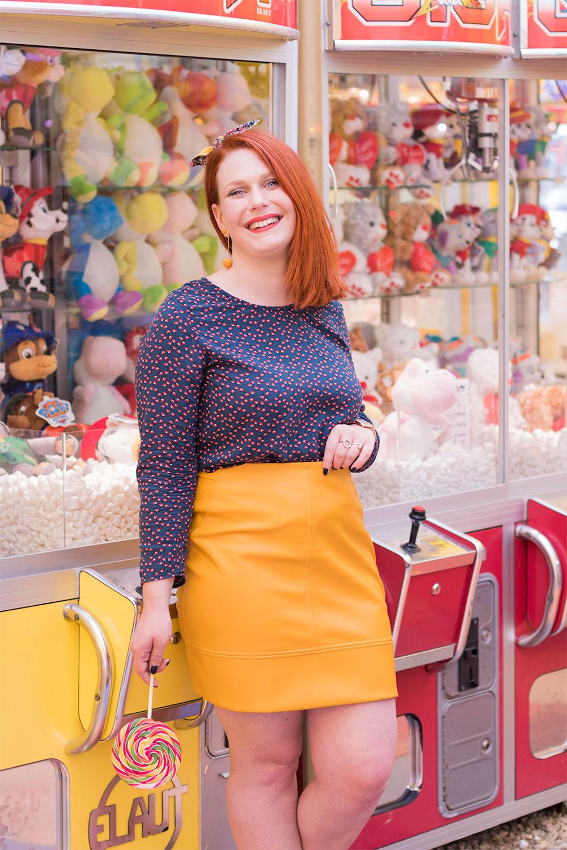 Contre les machines à grappins de la fête foraine en jupe jaune moutarde, blouse bleu canard, noeud dans les cheveux et sucette dans la main