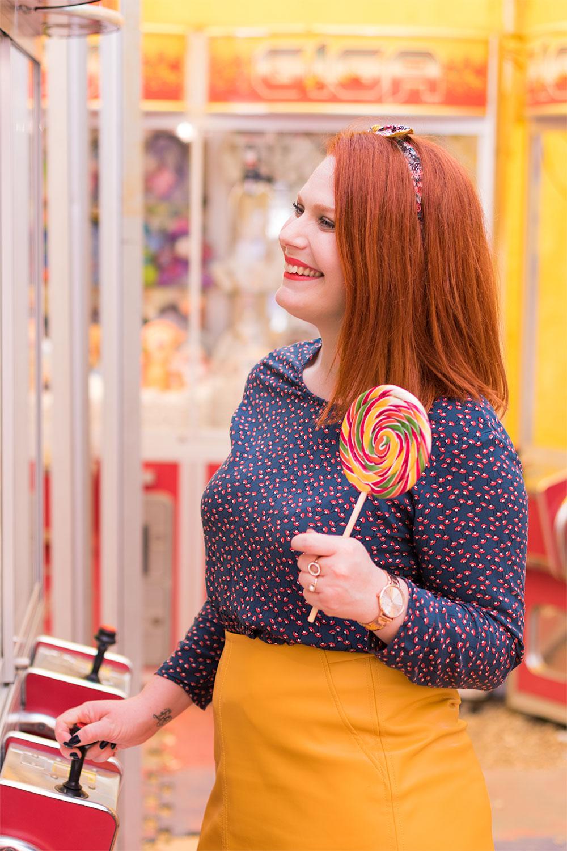 Blouse La Morue rentrée dans une jupe en simili cuir jaune moutarde avec une sucette multicolores dans les mains entrains de jouer aux machines à grappins de la fête foraine