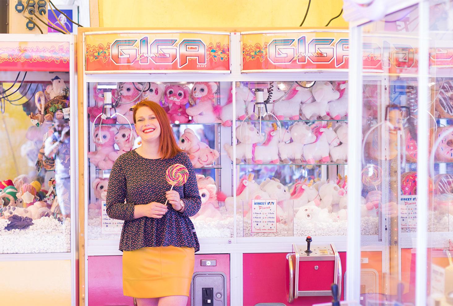 Blouse et noeud dans les cheveux La Morue, sucette multicolores à la main, devant les licornes des machines à grappins de la fête foraine