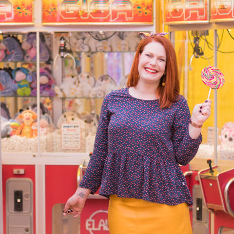 Blouse et noeud dans les cheveux La Morue, sucette colorée à la main et jupe moutarde, devant les machines à grappins à la fête foraine